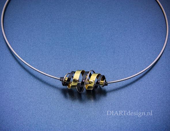 """Hanger, """"Slinger"""" uit geelgoud, zwart zirconium en titanium."""