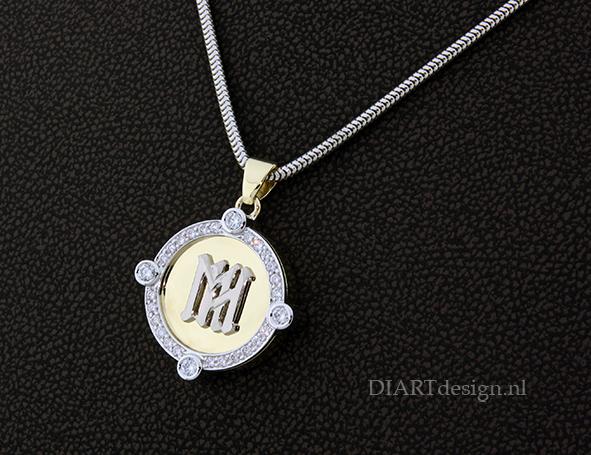 Urn hanger met monogram. Uit goud met briljanten.