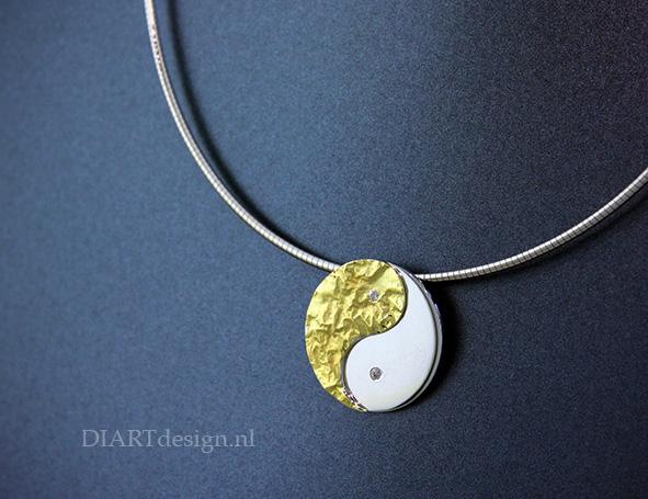 Yin en Yang hanger uit witgoud en geelgoud met briljant. In de achterkant kan as of haren bewaard worden.