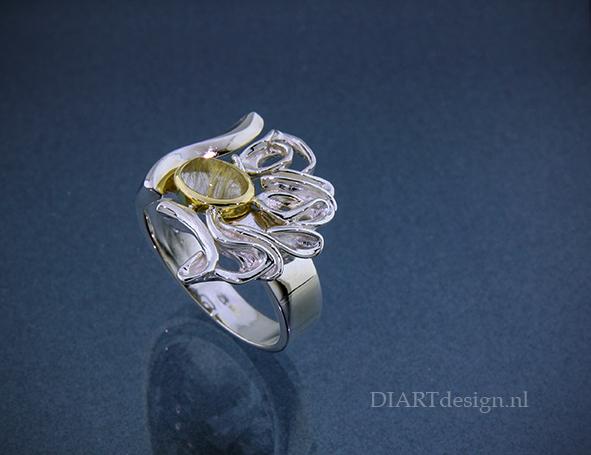 Zilveren ring. Strakke en natuurlijke vormen gecombineerd. Met een rutielkwarts in goud gevat.