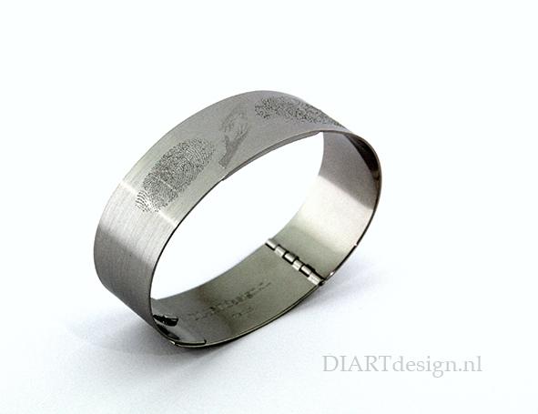 Armband uit titanium met vingerafdrukken en een persoonlijk symbool.