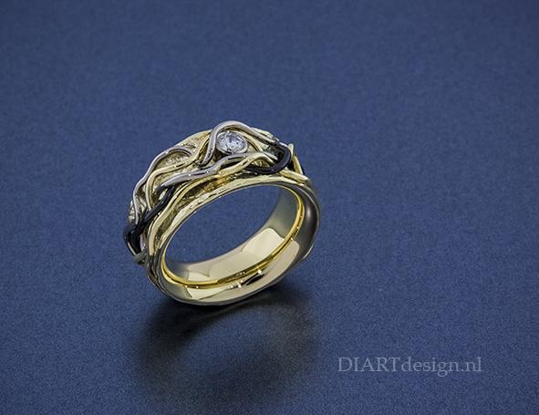"""""""Nest"""" ring, met levensdraden uit geelgoud, witgoud en zirconium en een briljant."""