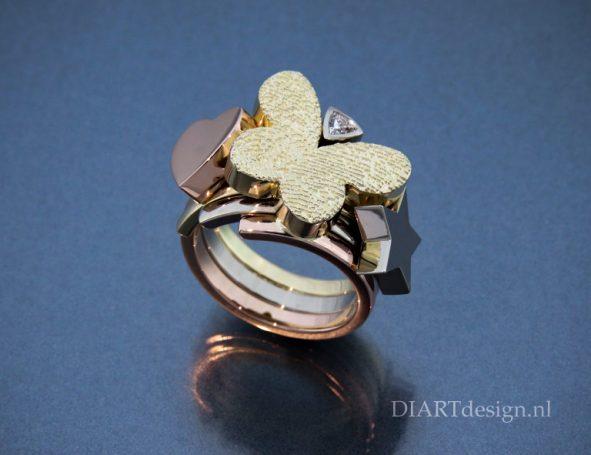 Ring met twee vingerafdrukken op de vlinder. Drie kleuren goud en een diamant.