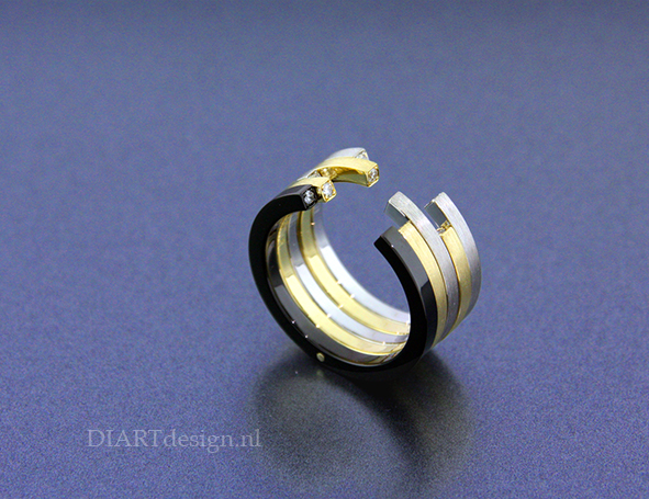 Ring uit witgoud, geelgoud en zwart zirconium met brillanten. Ring uit witgoud, geelgoud en zwart zirconium met brillanten.