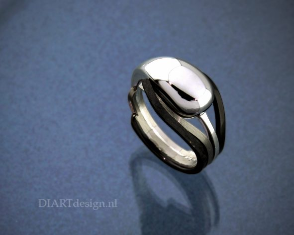 Urn ring uit witgoud, titanium en zwart zirconium.
