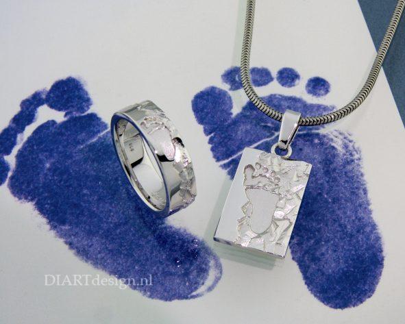 Kindervoetje op witgouden ring en hanger.