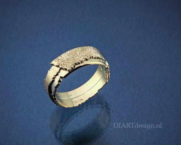 Ring met aan de binnenkant twee trouwringen verwerkt. Aan de buitenkant een vingerafdruk.