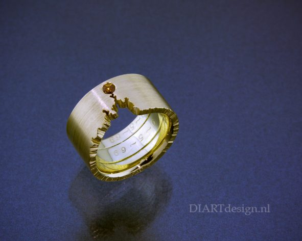 Ring om twee trouwringen heen gemaakt, met cognac kleurige briljant. De originele gravures zijn behouden.
