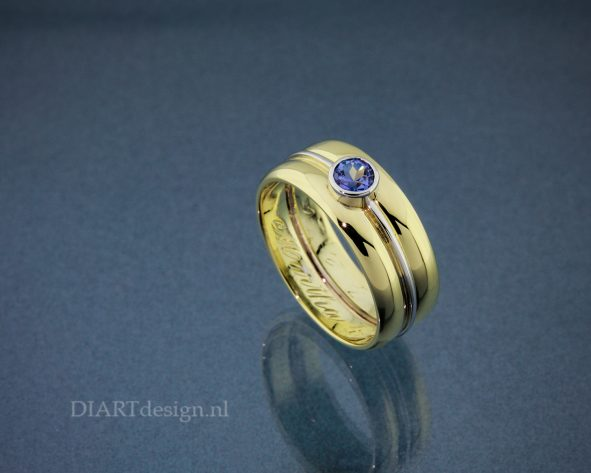 Ring gemaakt van twee trouwringen, met witgoud en tanzaniet. De originele gravures zijn behouden.