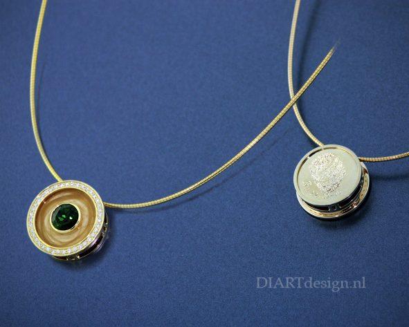 Gouden urn hanger met met haren zichtbaar verwerkt. Met briljanten en groene toermalijn. Op de achterkant een vingerafdruk gegraveerd.