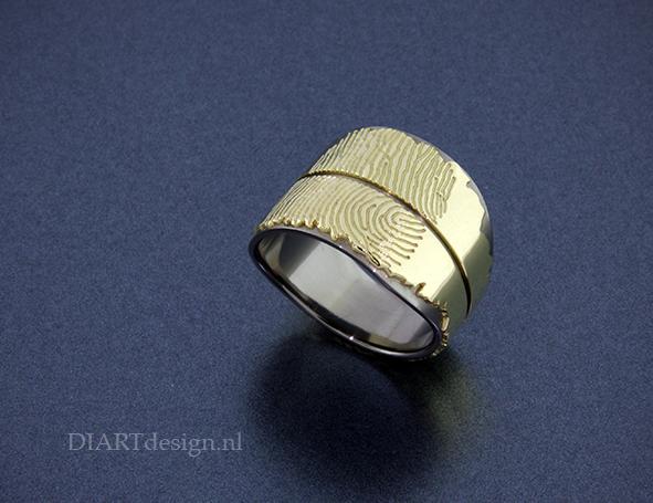 Ring uit titanium en geelgoud en twee vingerafdrukken.