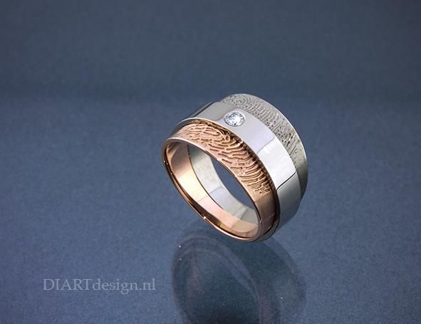Ring uit witgoud en roodgoud met een brillant en twee vingerafdrukken.